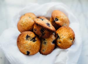 lemony blueberry muffins in a basket with a white dish towel