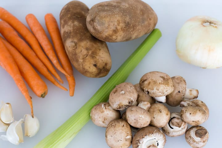 carrots, potatoes, garlic celery, onion and mushrooms on a cutting board