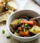 white bowl of guinness beef stew with irish soda bread in background