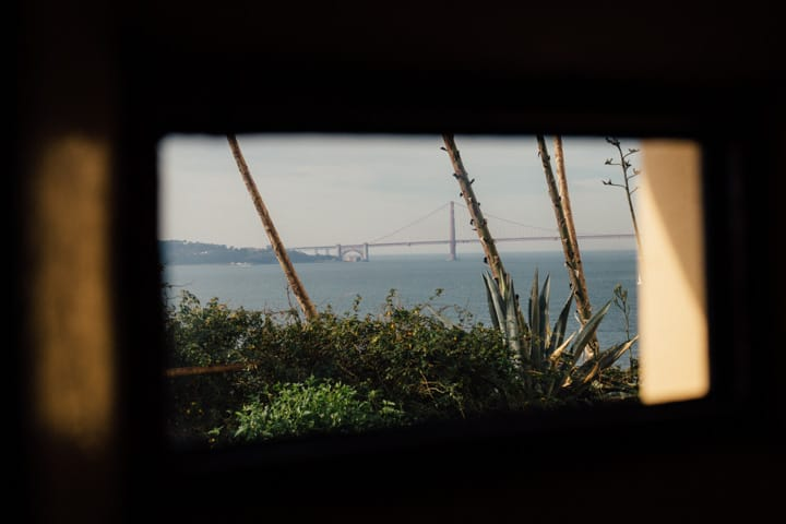 golden gate bridge through small window opening in alcatraz penitentiary