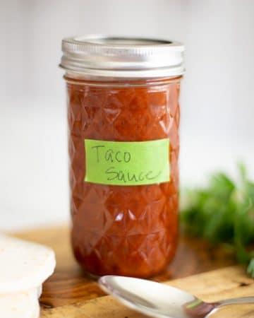 mild taco sauce in a mason jar with flour tortillas and an avocado