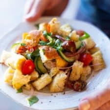 """Panzanella or """"Bread Salad"""" is a versatile recipe loaded with cucumbers, tomatoes, and olives and is great on its own, or alongside your favorite grilled meat. Since cucumbers and tomatoes are delicious year-round, this Panzanella recipe is great in the summer when you don't want to heat up the kitchen, or in the cooler months when you're craving a lighter, easy to prepare meal. #panzanella #breadsalad"""