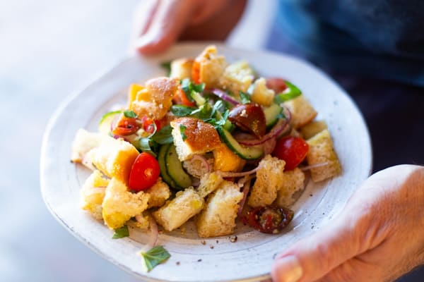 "Panzanella or ""Bread Salad"" is a versatile recipe loaded with cucumbers, tomatoes, and olives and is great on its own, or alongside your favorite grilled meat. Since cucumbers and tomatoes are delicious year-round, this Panzanella recipe is great in the summer when you don't want to heat up the kitchen, or in the cooler months when you're craving a lighter, easy to prepare meal. #panzanella #breadsalad"