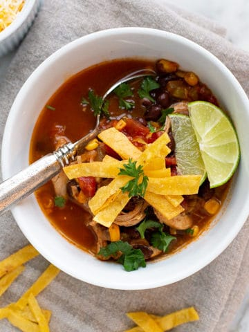 Easy Chicken Tortilla Soup is a hearty, delicious soup filled with chicken, green chile, corn, and black beans in a tomato broth. This soup is full of flavor without being too spicy. Serve it with fried tortilla strips and cheese for the ultimate Tex-Mex lunch or dinner!