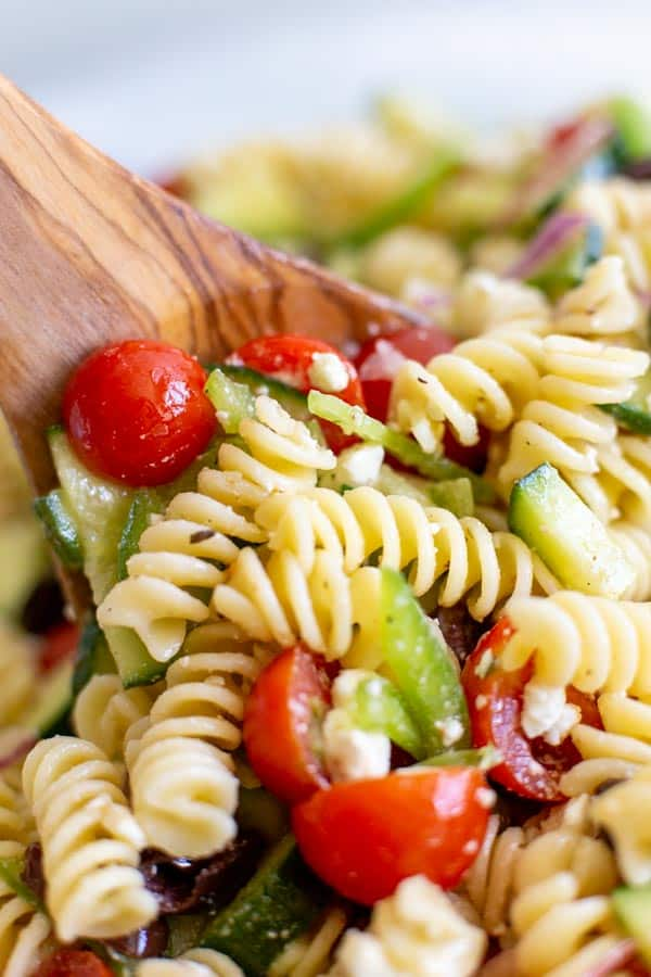 close up of greek pasta salad with a wooden spoon in bowl
