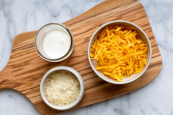a bowl of shredded cheddar cheese, shredded parmesan cheese and heavy cream on a wooden board