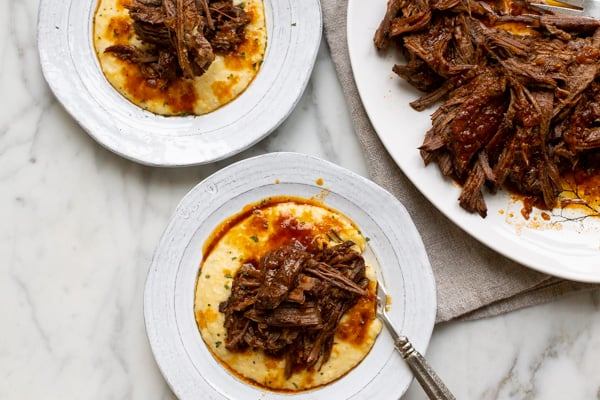 instant pot beef brisket on a white plate with grits
