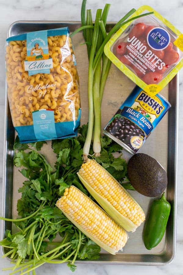 Pasta, corn, tomatoes, black beans, cilantro, avocado, and jalepeno ingredients for Mexican Pasta Salad recipe.