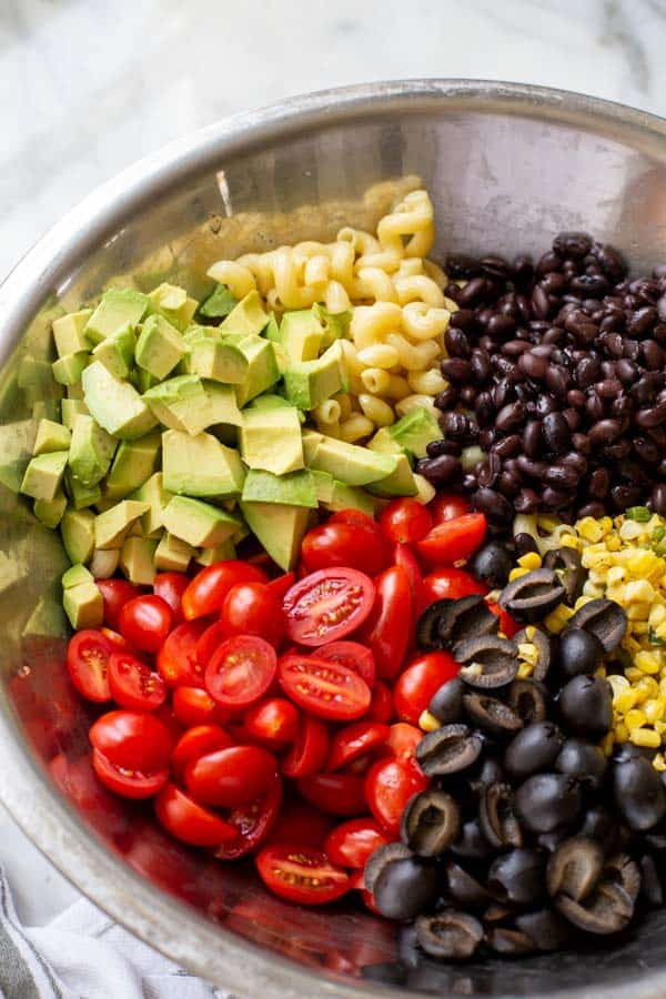 A bowl of corn, avocados, tomatoes, black olives, and black beans for Mexican pasta salad recipe.