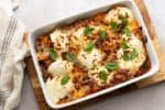 baked ravioli in a white casserole dish with a dishtowel in the background