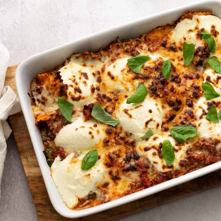 baked ravioli topped with fresh basil in a white casserole dish