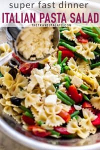 Italian dressing pasta salad in a large bowl with feta cheese being added. pinable image.