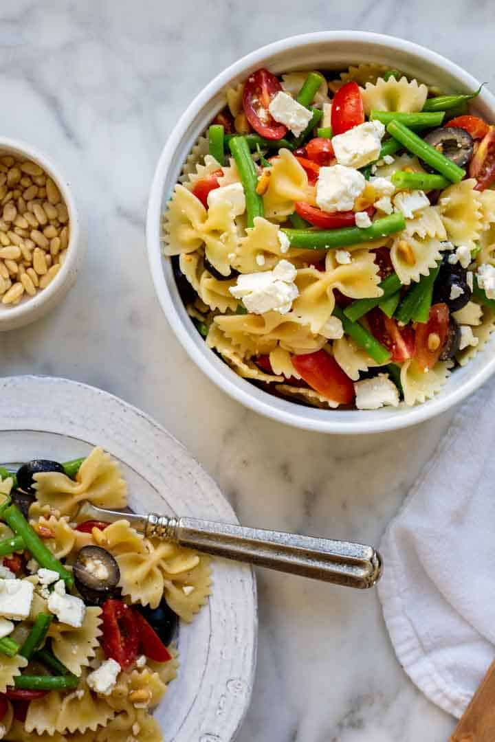 a bowl and plate filled with Italian dressing pasta salad with pine nuts in a small bowl