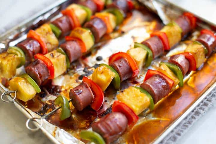 cooked sausage skewers on cooking sheet