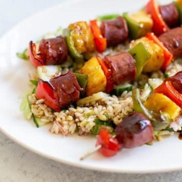 a plate of sausage skewers over rice