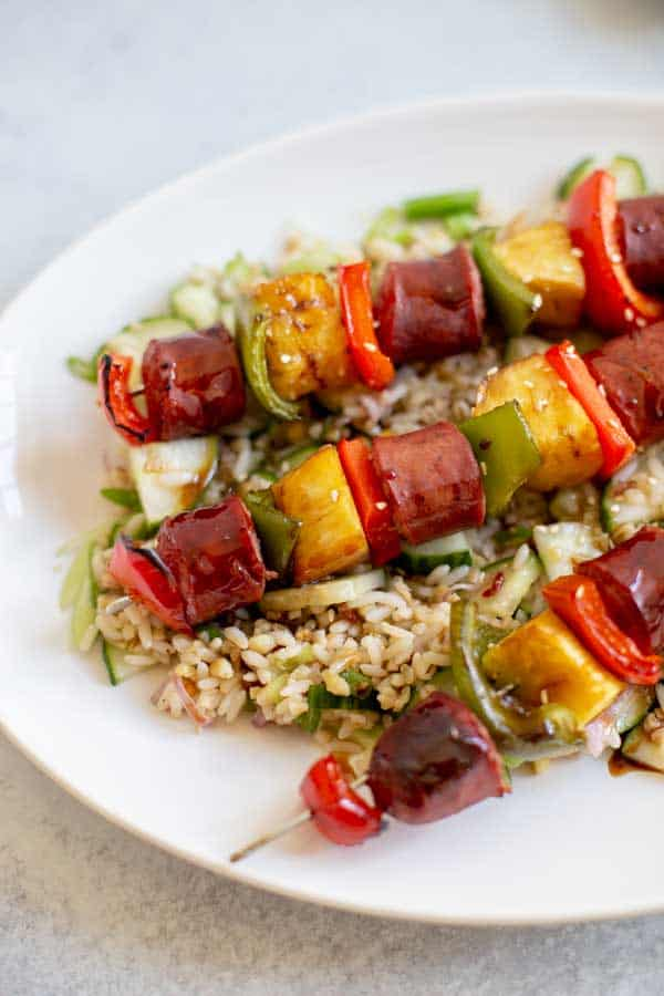 plate of sausage skewers over a bed of rice