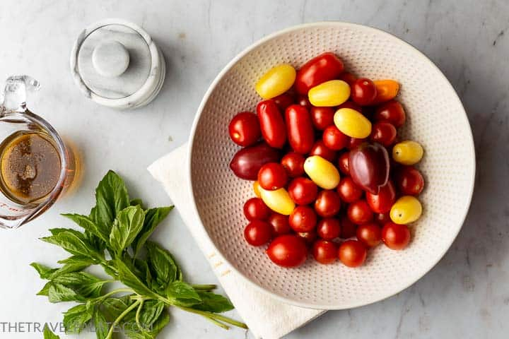 bowl of cherry tomatoes with fresh basil, olive oil and salt in the background