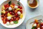 cherry tomato caprese salad in a bowl with dressing and plate in background