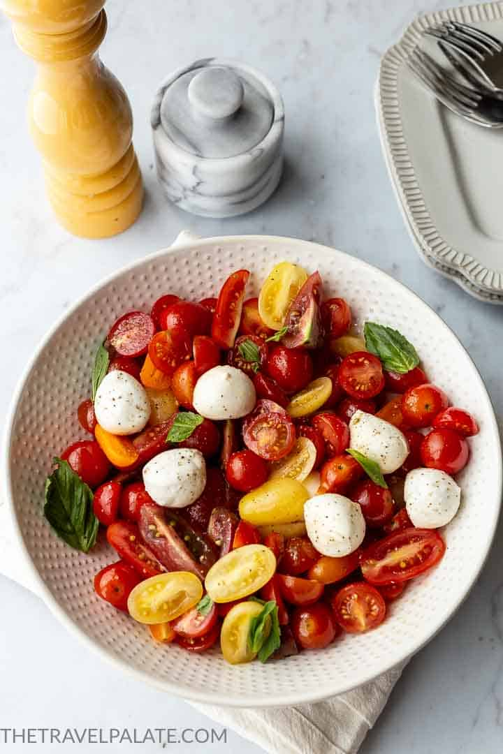 bowl of cherry tomato caprese salad with salt and pepper in background
