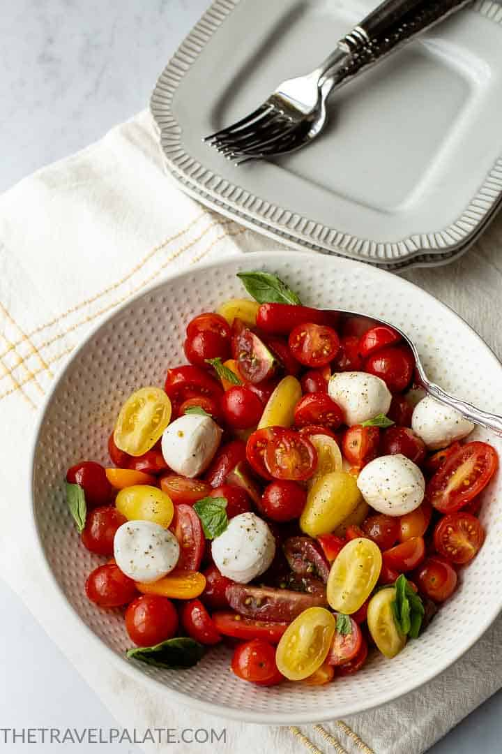 bowl of cherry tomato caprese salad with forks and plates in background