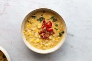 bowl of jalepeño corn chowder with a tomato and bacon garnish