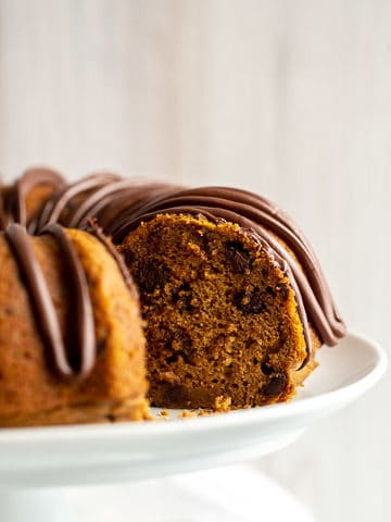 a pumpkin chocolate chip bundt cake on a white cake stand
