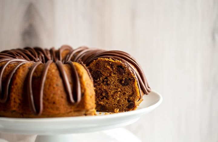 a pumpkin chocolate chip bundt cake on a white cake stand