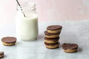 sunbutter cups stacked with a glass of milk in the background