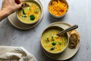 two bowls of easy broccoli cheese soup with a hand dipping bread; shredded cheddar cheese in the background