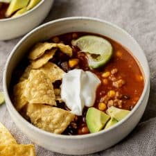 a bowl of taco soup with crushed chips, sour cream, avocado and lime wedge
