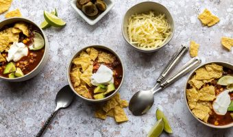 bowls of taco soup, cheese, spoons, jalepenos and crushed tortilla strip