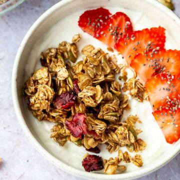 Granola and sliced strawberries over yogurt in a white bowl
