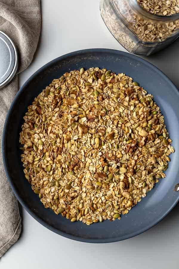 Toasting walnuts and pumpkin seeds in a non-stick skillet.