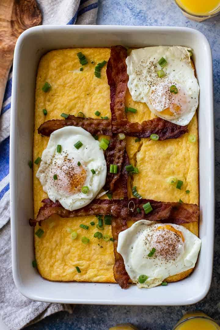 white casserole pan with grits, bacon strips and 3 fried eggs