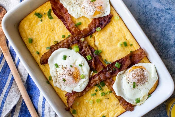 grits recipe in white casserole dish topped with bacon strips and fried eggs