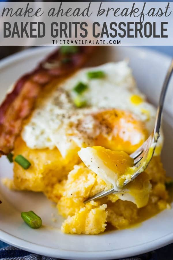a fork taking a bite of an egg over grits casserole with a piece of bacon in the background