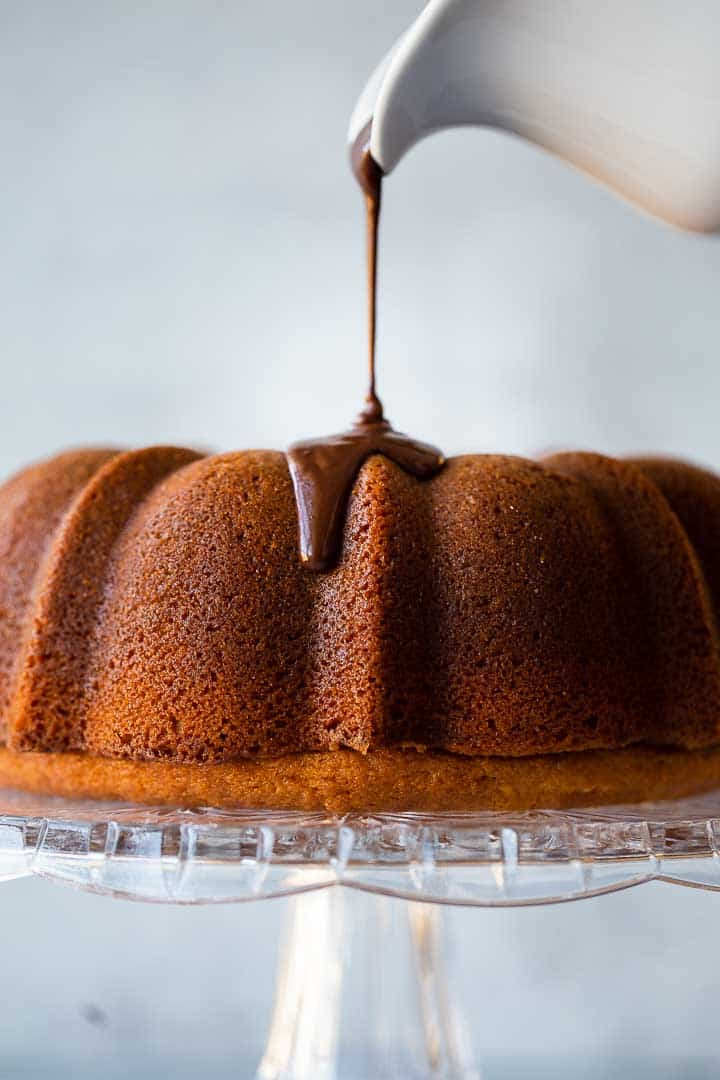 chocolate ganache being poured over a bundt cake