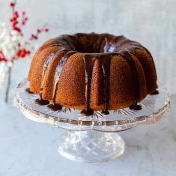 butterscotch bundt cake on a crystal cake stand with red berries in the background