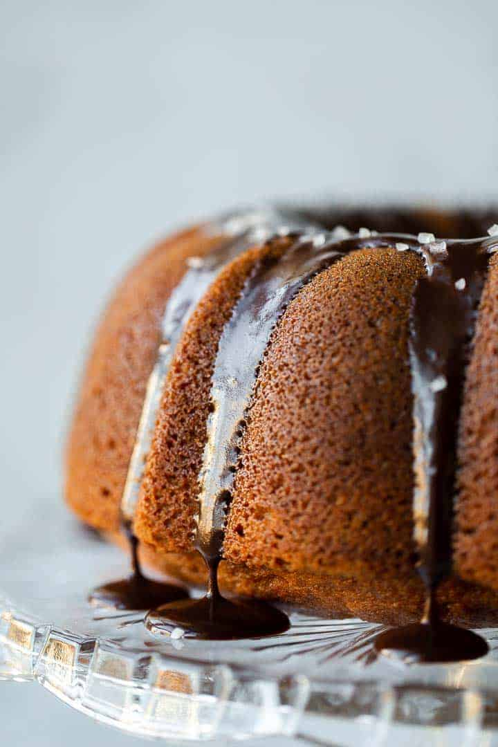 butterscotch bundt cake on a crystal cake stand with chocolate ganche and sea salt