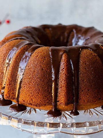 butterscotch bundt cake on a crystal cake stand with red and white flowers in the background