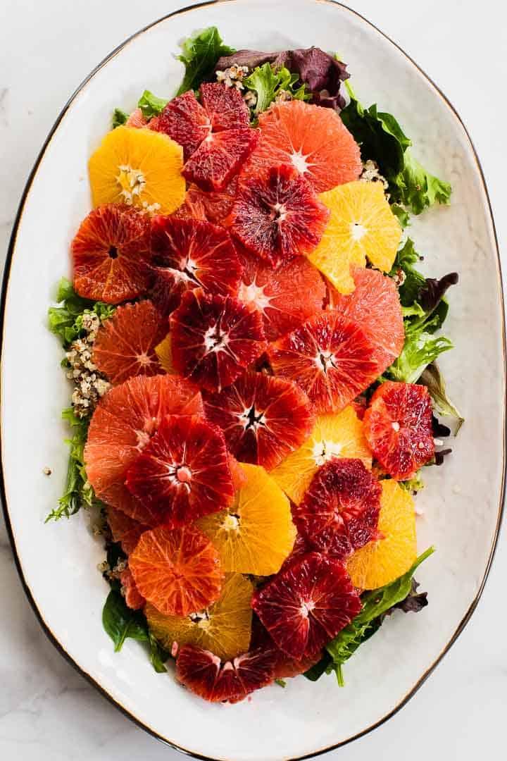 assembling salad on a white platter
