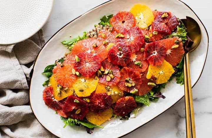 close up of citrus salad on a white platter with gold salad servers