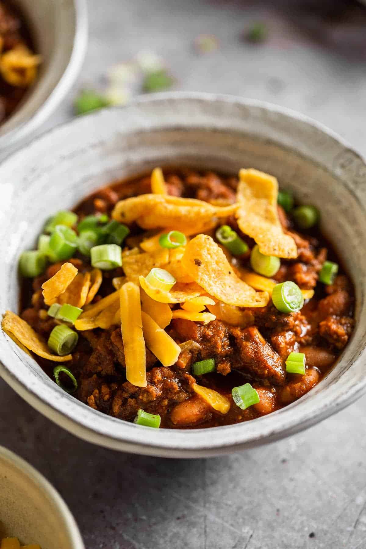 bowl of chili topped with fritos and green onions