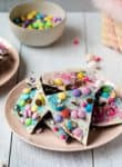 broken pieces of candy bark on a pink plate