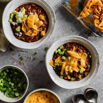 two bowls of chili topped with frito chips with green onion, cheese, and bag of fritos in background