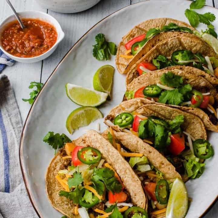 several tacos on a white platter with a bowl of salsa in the background