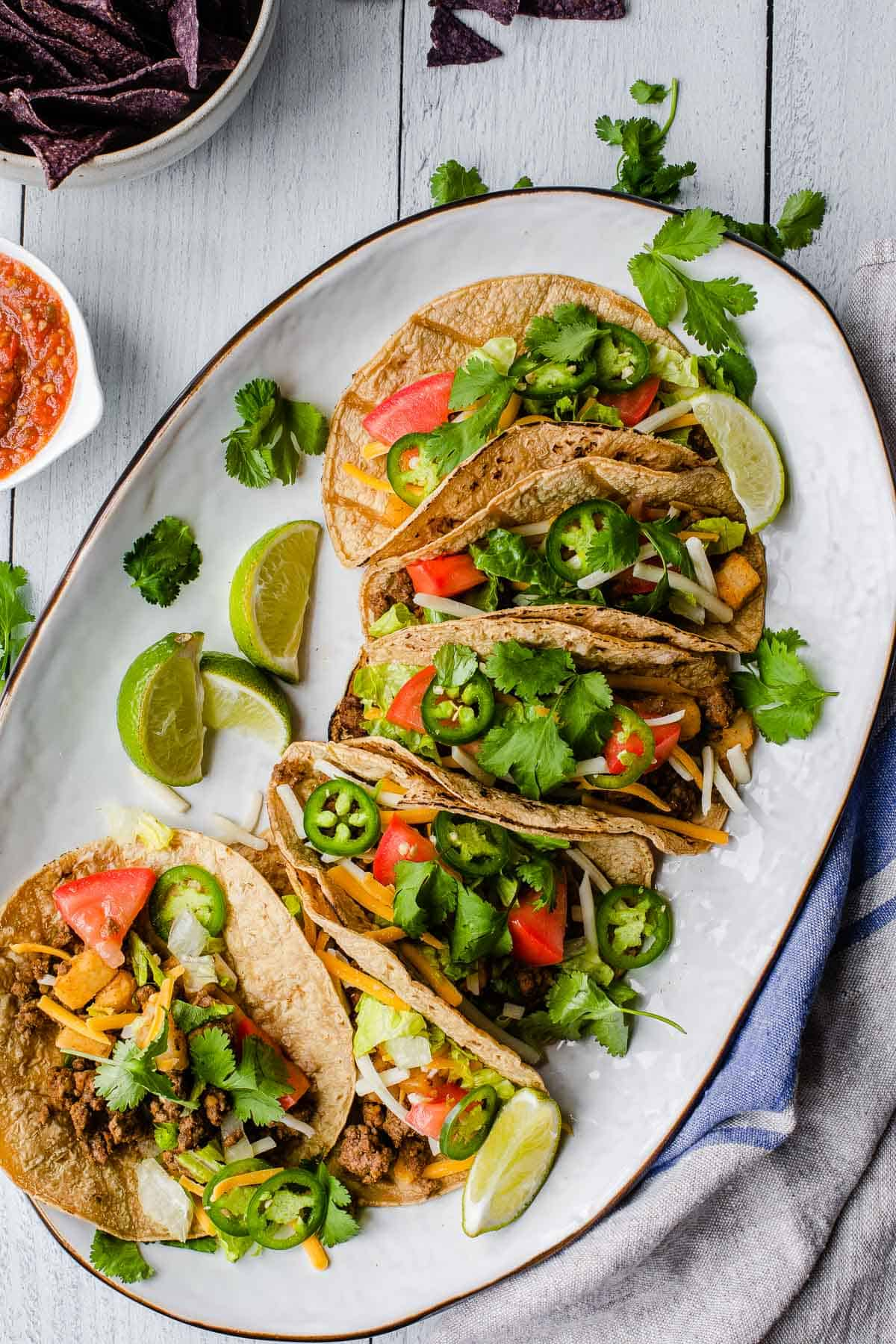 several tacos on a white platter