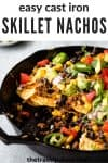 close up view of nachos in a cast iron skillet with text overlay