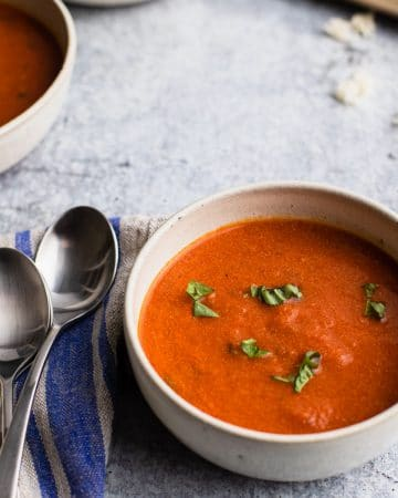 a bowl of tomato basil soup with two spoons on the left