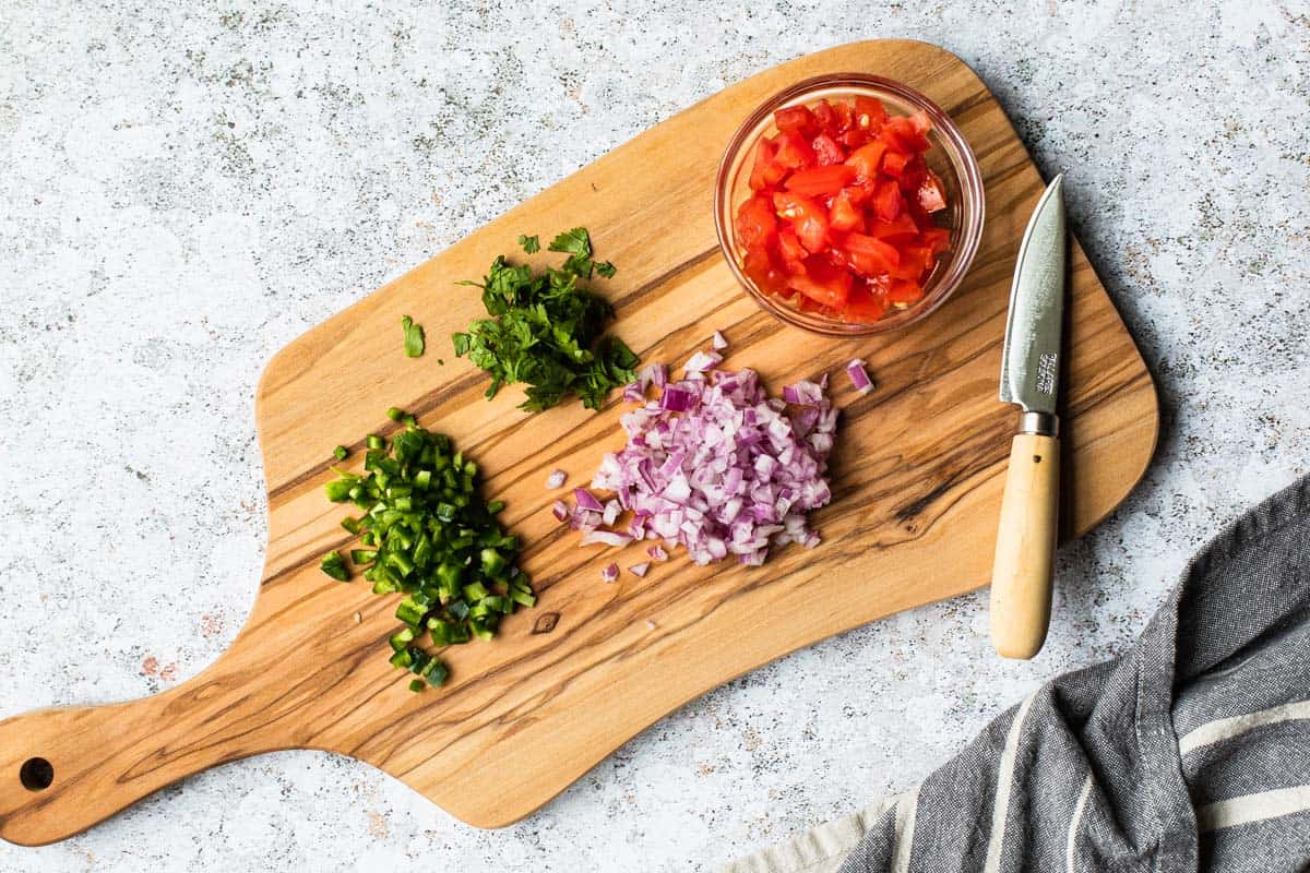 chopped produce on a cutting board with a knife off to side